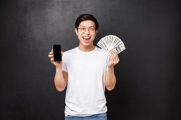 Концепция технологии, деньги и призы. взволнованный счастливый азиатский победитель мужского пола получает награду за завершение онлайн-конкурса, показывая денежный приз и экран смартфона, довольный улыбкой