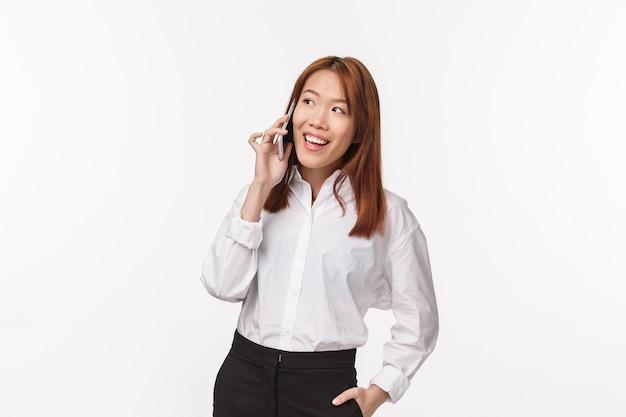 Портрет элегантной успешной азиатской бизнес-леди, звонящей человеку, держащему мобильный телефон возле уха и улыбающемуся, организующему встречу через смартфон, заказывающему доставку еды в офис,