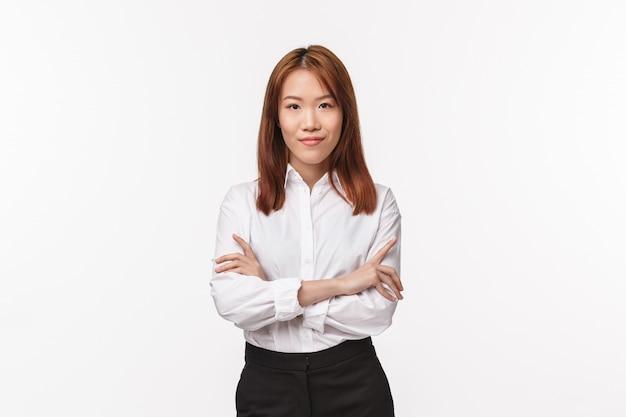 専門家、キャリア、ビジネスコンセプト。ホワイトカラーのシャツを着た深刻な格好の成功した女性起業家、クロスハンド胸の自信、笑顔とカメラの自信