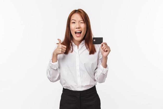 Портрет довольной и уверенной в себе симпатичной азиатки в рубашке, подмигивающей под камеру, показывает большой палец вверх и кредитную карту, рекомендует банковское обслуживание, в восторге от качества,