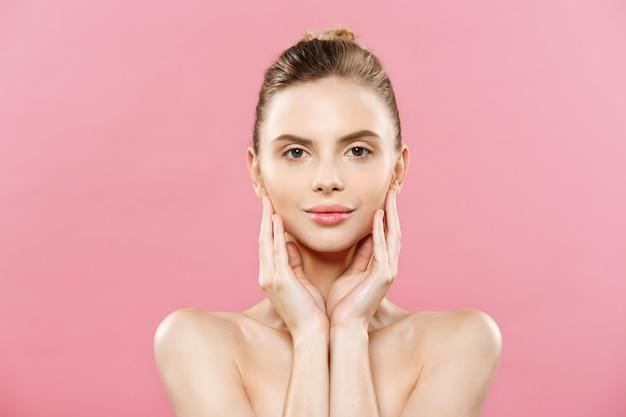 美容の概念 - きれいな肌、自然なメイクアップは、コピースペースと明るいピンクの背景には、美しい白人の女性。