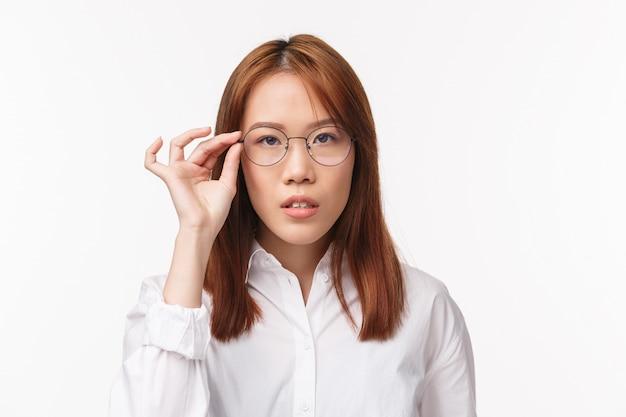 Портрет крупным планом азиатской милой молодой девушки в белой рубашке, пробует новые прописанные очки, выбирает очки в магазине оптики, смотрит в камеру, решительно слушает, стоя белый