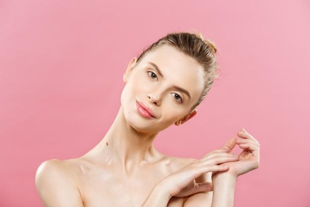 Концепция красоты - красивая женщина кавказа с чистой кожей, естественный макияж, изолированных на ярко-розовый фон с копией пространства.