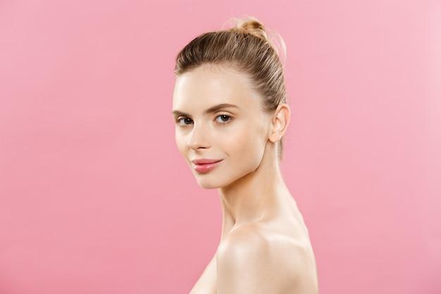 Концепция ухода за кожей - очаровательная молодая женщина кавказа с идеальным составом фото состава брюнетка девушка. изолированные на розовом фоне с копирования пространство.