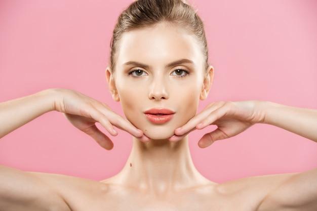 美容の概念 - クローズアップ美しい自然な肌と魅力的な白人の女の子の肖像画は、コピースペースとピンクの背景に分離。