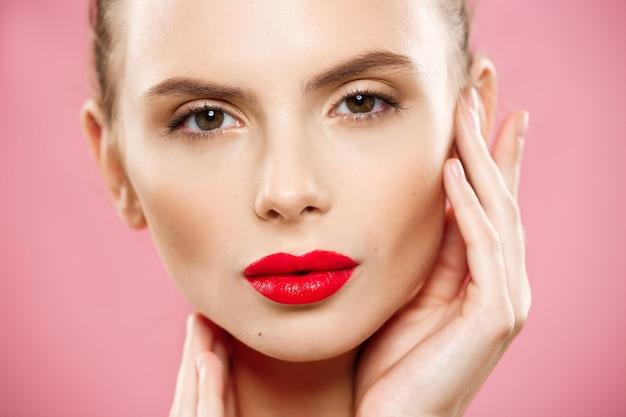 美しさの概念 - クローズアップ豪華な若いブルネット女性の顔の肖像画。美容モデル明るい眉、完璧なメイクアップ、赤い唇、彼女の顔に触れる女の子。ピンクの背景に