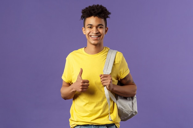 Снова в школу, концепция университета. портрет веселого красавца-студента рассказывает своим одноклассникам о летних каникулах, показывает рекомендации, одобряет большие пальцы, держит рюкзак