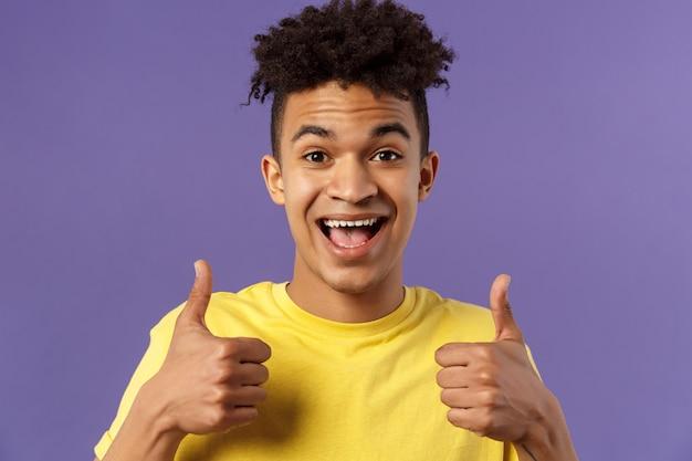 Крупный портрет восторженного, жизнерадостного хипстерского парня с афро-стрижкой, с чем-то соглашается, показывает большой палец вверх, улыбается с радостью, рекомендует хороший продукт, любит и одобряет план,