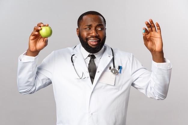 Здравоохранение, медицина и концепция здорового образа жизни. скептически красивый афро-американский врач выглядит неуверенно и нерешительно, а таблетка показывает наркотики и яблоко, здоровое питание или лекарства