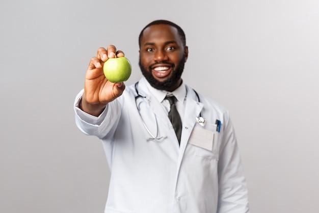ヘルスケア、医学、健康的なライフスタイルのコンセプト。一日アップル。陽気なハンサムなアフリカ系アメリカ人の医師が患者に青リンゴを与え、果物に果物とビタミンを食べさせて