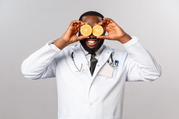 ヘルスケア、健康的な食事と病気の概念。白衣を着た幸せな面白いアフリカ系アメリカ人男性医師、診療所で横になっている子供の気分を高め、患者がより多くのビタミンを食べることを説明し、目にオレンジをかざす