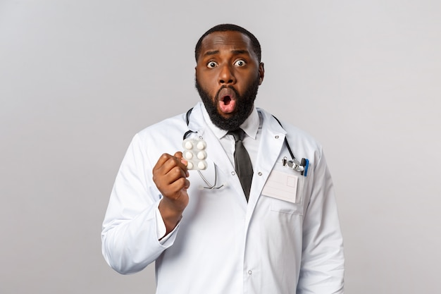 Концепция гриппа, болезней, здравоохранения и медицины. шокированный афро-американский врач понимает, что пациент неправильно принимал таблетки, не следовал предписаниям, задыхался и держал лекарства