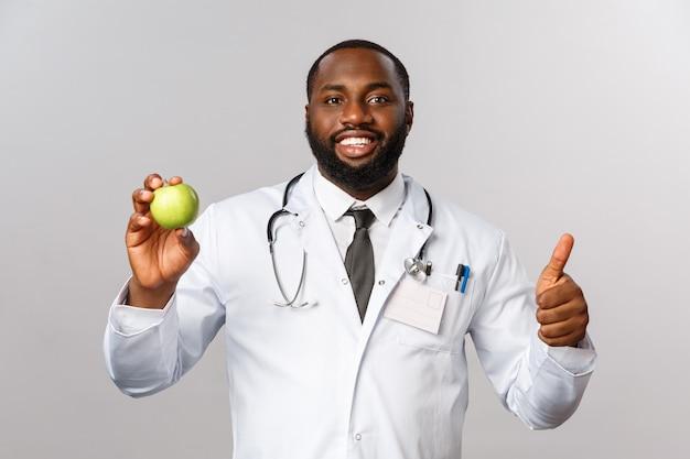 Здравоохранение, медицина и концепция здорового образа жизни. уверенно красивый афро-американский врач рекомендует есть фрукты, держать зеленое яблоко, улыбаться довольный и большой палец вверх, пациенту нужны витамины