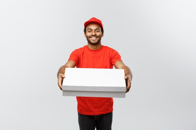 Концепция доставки - портрет красивой афро-американской доставки пиццы человек. изолированные на фоне серой студии. копирование пространства.