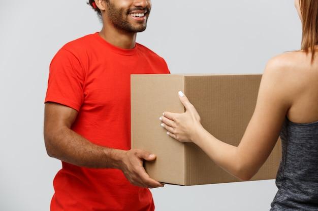 Концепция доставки - красивый афроамериканец доставки человек дает пакет для домовладельцев. изолированные на фоне серой студии. копирование пространства.