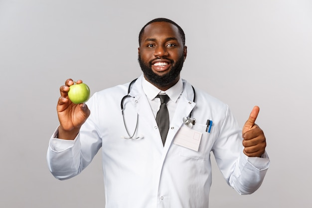 Уверенно красивый афро-американский врач рекомендует есть фрукты, держать зеленое яблоко, улыбаться довольный и большой палец вверх, пациенту нужны витамины
