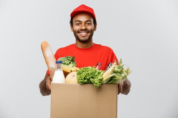 配達のコンセプト - 店から食料品や飲み物のパッケージボックスを運ぶハンサムなアフリカ系アメリカ人の配達人。灰色のスタジオの背景に分離。スペースをコピーします。