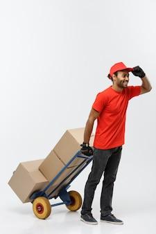 配達の概念 - 肖像画のハンサムなアフリカ系アメリカ人の配達人または宅配便箱のスタックで手のトラックを押す。灰色のスタジオの背景に分離。スペースをコピーします。