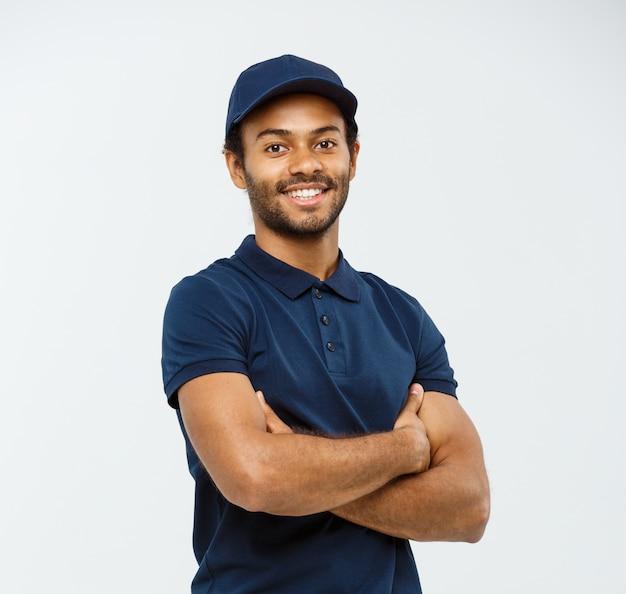デリバリーのコンセプト - 幸せなアフリカ系アメリカ人の配達人は灰色のスタジオの背景に隔離された腕を越えたスペースをコピーします。
