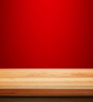 ぼんやりと製品の配置のための赤いクリスマスの背景と空の木製のテーブルクリスマスの壁紙の背景