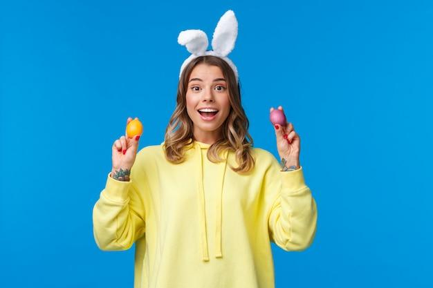 Праздники, традиции и концепция праздника. милая белокурая кавказская сестра хочет играть в игру с братом, держащим два расписных пасхальных яйца и улыбающихся, одетых в кроличьи уши, голубая стена