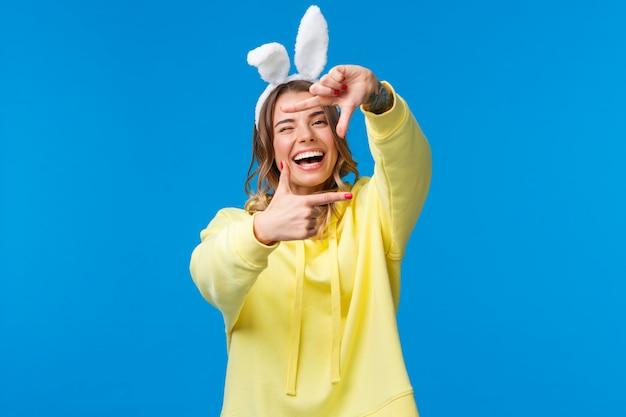 Праздники, традиции и концепция праздника. счастливая харизматичная молодая белокурая девушка с татуировкой на руке, ищущая правильный угол для выстрела или момент захвата, смеясь, смотрит через рамки, носит уши кролика