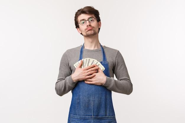 Концепция малого бизнеса, финансов и карьеры. портрет милого жадного молодого человека не хочет тратить деньги, обнимает деньги и дуться, так как нужно платить за аренду, копит зарплату на новый компьютер, белая стена