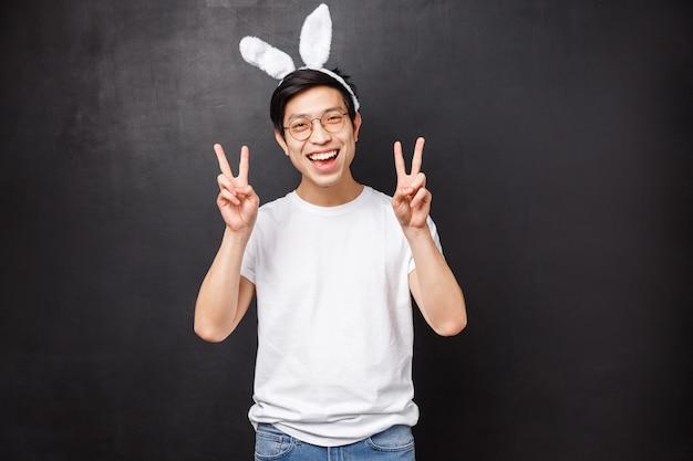 Праздники, вечеринки и концепция пасхи. веселый азиатский симпатичный парень в ушах кролика и в очках, показывающих знаки мира, смотрит каваи, празднующий православный день на весну, стоящий черная стена радостная