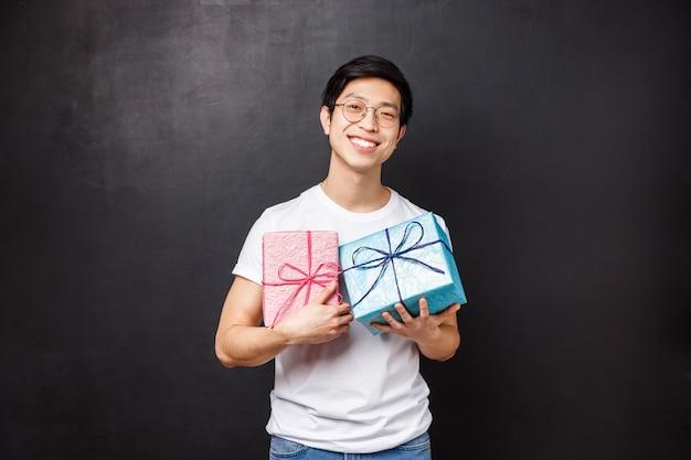 Празднование, праздники и концепция образа жизни. портрет милого и красивого парня приготовил подарки для своего партнера, держа в руках две подарочные коробки розового и синего цвета, с гордой улыбкой, черная стена