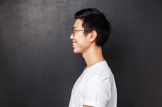 Профиль портрет счастливого улыбающегося азиатского человека в белой футболке, смотрящего на пустое пространство слева, дружелюбно улыбаясь, представляя себя на фоне черной стены, людей, эмоций и рекламы