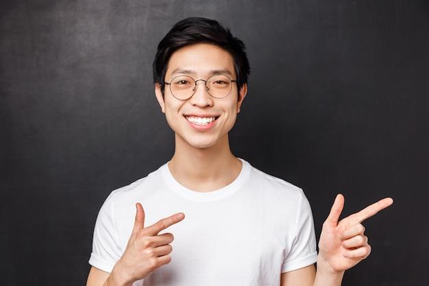 Макро портрет дружелюбного улыбающегося азиатского человека в белой футболке и очках уверенно, указывая пальцем прямо на баннер промо или компании, дают рекомендации, черная стена