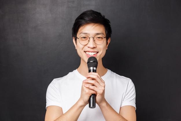 Досуг, люди и музыкальная концепция. портрет мило улыбающегося азиатского человека в белой футболке, держащего микрофон обеими руками, поющего песню на вечеринке караоке, выступающего перед аудиторией, черная стена