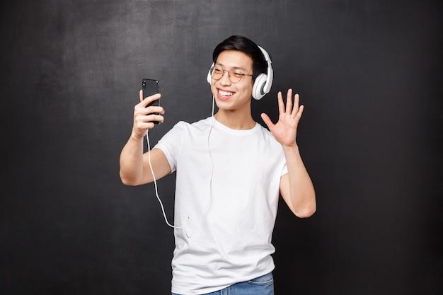 Концепция технологии, гаджеты и люди. портрет дружелюбного улыбающегося красивого азиатского мужчины в футболке, надевают наушники, машут рукой, здороваются, разговаривают по видео-звонку, используя мобильный телефон, контактируют с другом