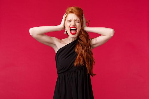 黒のドレスで苦しんでいると圧力の若い赤毛の女性の肖像画、感情の制御を失う落ち込んで悲鳴を上げる、否定で頭に手をつないで、悪い真実、赤い壁を見つけた