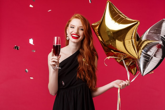 Празднование, праздники и концепция партии. беззаботная красотка рыжая развлекается с друзьями, устраивая день рождения, надевает черное платье, держит воздушные шарики и пьет шампанское с конфетти в воздухе
