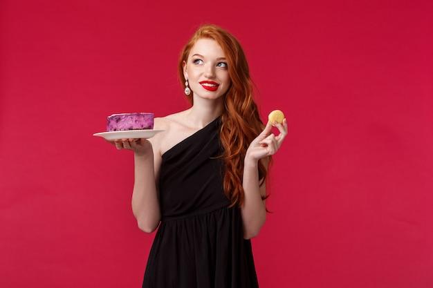 Вдумчивая и мечтательная великолепная стройная рыжая женщина в черном платье думает о еде десерта, заботясь о своем теле, отводит взгляд, обдумывает и улыбается, держит печенье и торт