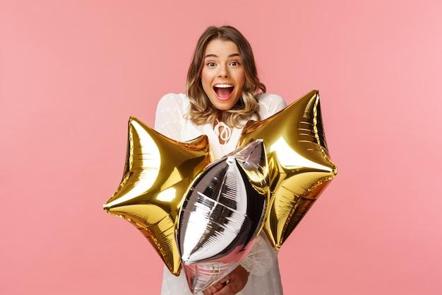 Праздники, торжества и женщины концепции. счастливая обаятельная и удивленная девушка поздравляется с днем рождения, держит воздушные шары в форме звезды и радостно улыбается на розовой стене