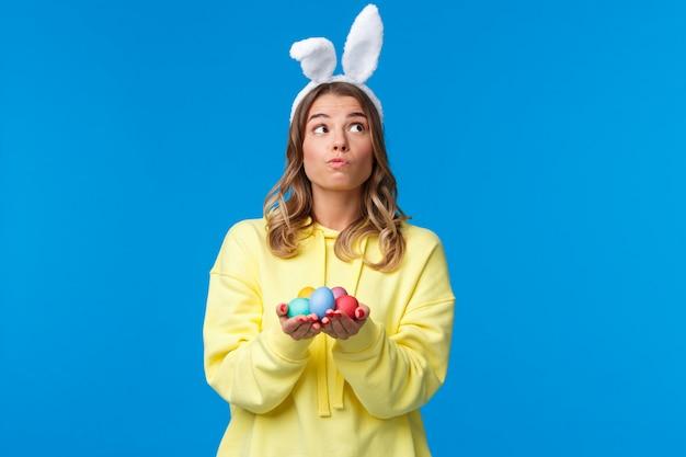 Задумчивая милая кавказская девушка в кроличьих ушах думает, смотрит вдумчиво и мечтательно, держит пасхальные яйца, решает, где спрятать ее во время традиционной праздничной игры, на синей стене