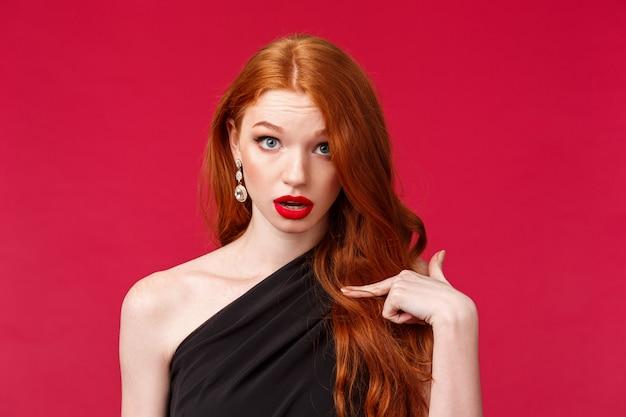 誰、私。黒いドレスを着たショックを受けて驚いた驚愕の赤毛の女の子は、質問されて混乱し、赤い壁の上で自分自身を指しているか、何かに取り上げられているか、非難されているかのように不信を凝視している