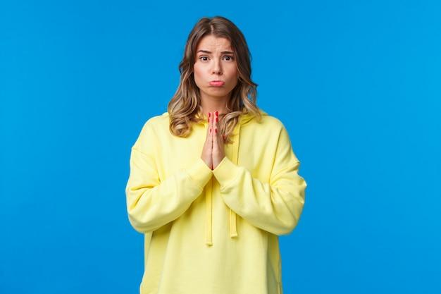 Милая идиотская подружка, просящая купить ей то, что она хочет, со скидкой, держась за руки в молитве, надутой и выглядя умоляющей, прося милости, встать на синюю стену