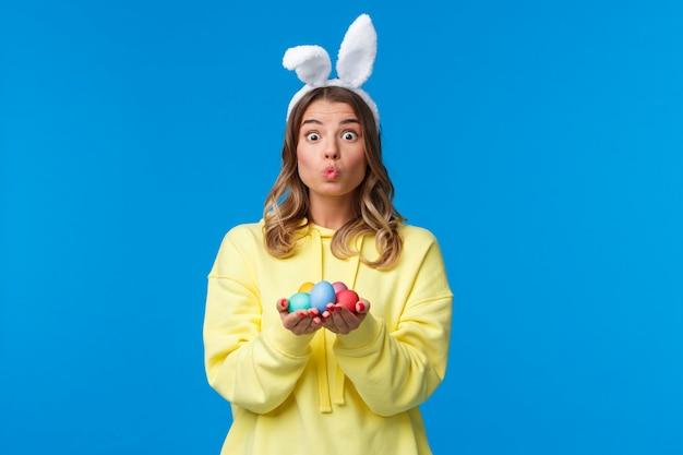 Праздники, традиции и концепция праздника. глупая милая кавказская белокурая девушка подарит вам пасхальные яйца, раскрасит их на праздник, покажет выражение лица поцелуя и носит кроличьи уши на синей стене