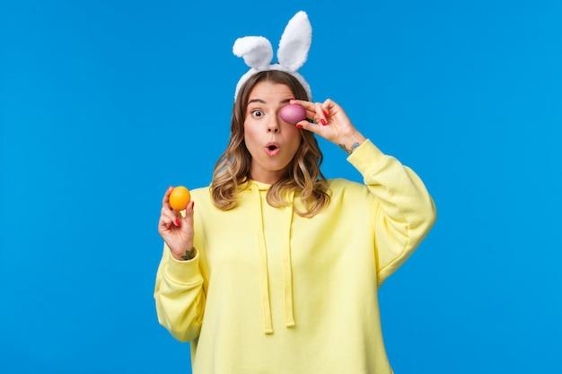 Праздники, традиции и концепция праздника. удивленная милая европейская блондинка в ушах кролика, выглядишь взволнованной и удивленной, держа в руках две расписные пасхальные яйца на синей стене