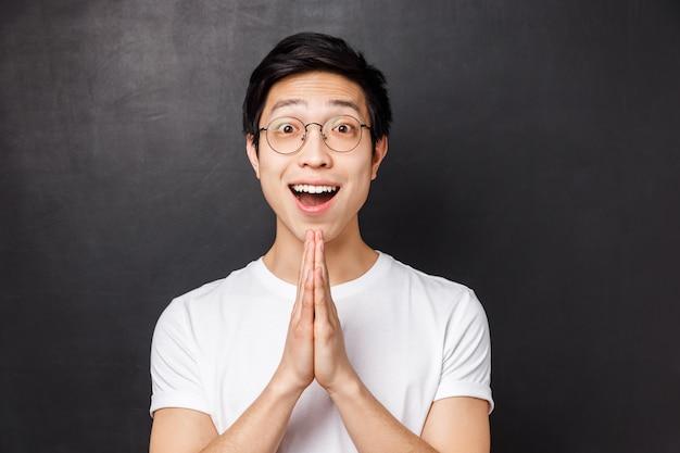 Портрет крупного плана обнадеживающего и благодарного молодого счастливого азиатского парня получает помощь после просить друга, говоря спасибо, держит руки в молитве, ценит жест, стоя на черной стене