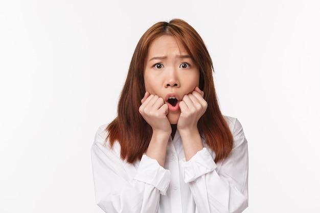 Макро портрет испуганной робкой азиатской девушки, паниковавшей, кусающей пальцы, выглядящей испуганной, хмурой и обеспокоенной, испуганной, смотря интересный фильм ужасов, белая стена