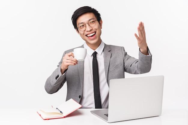Портрет талии вверх позабавленного, счастливого успешного молодого азиатского бизнесмена приглашая человека заходить в его офис, сидя за столом расслабленно пить кофе из чашки, указывая на что-то хвастливое