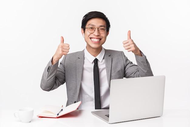 Талия-вверх портрет довольного, счастливого улыбающегося азиатского офис-менеджера, сидящего за столом с ноутбуком, ноутбуком, пьющего кофе, работающего, показывающего большие пальцы, все хорошо, на белой стене