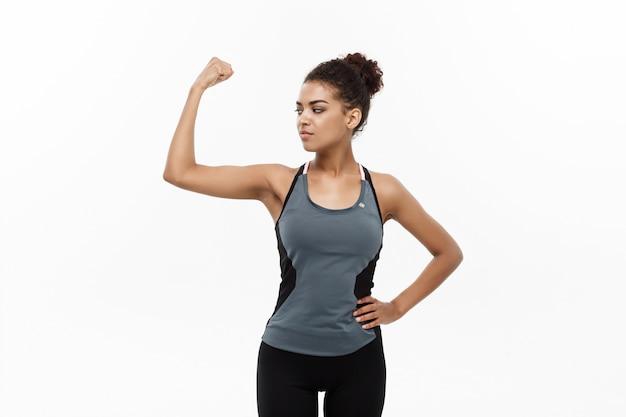 Здоровая и фитнес концепция - портрет молодой красивой афро-американец, показывая ее сильные мышцы с уверенным веселым выражением лица. изолированные на белом фоне студии.