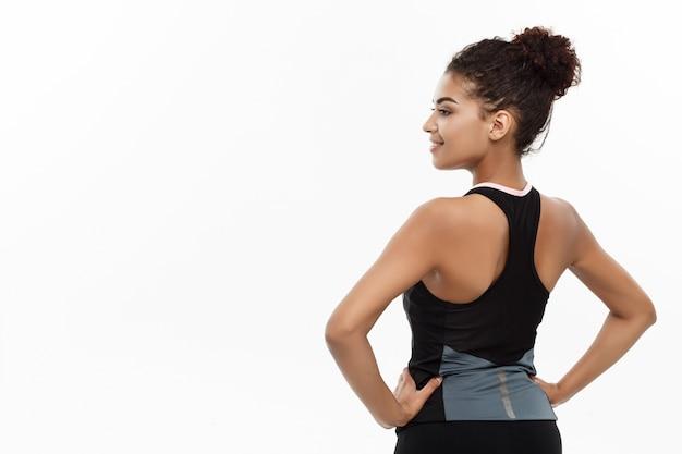 Концепция «здоровая и пригодная» - портрет молодого красивого афроамериканца, демонстрирующего ее мышцы спины с уверенным весёлым выражением лица. изолированные на белом фоне студии.
