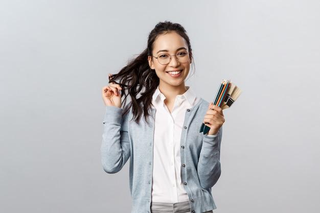 Хобби, творчество и концепция искусства. веселая, талантливая и креативная милая азиатская девушка в очках, кокетливо играющая с волосами и улыбающаяся, держащая цветные карандаши и малярные кисти, серая стена