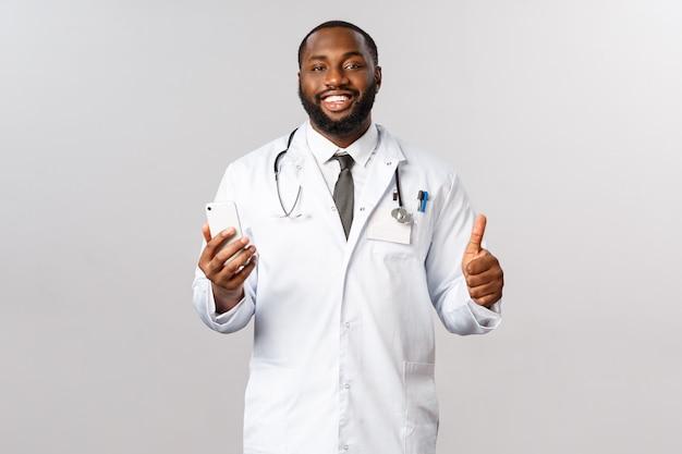 Концепция пандемии и онлайн-медицины. красивый улыбающийся афро-американский врач показывает большой палец вверх, держите смартфон, рекомендует медицинскую помощь врачу или пациенту, обратитесь в службу поддержки или в приложение
